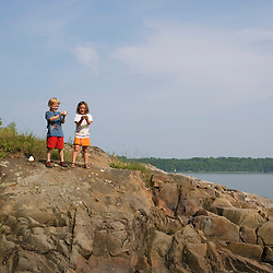 Young children (age 5) explore the rocks in Marquoit Bay in Brunswick, Maine.