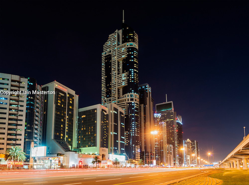 Modern skyscrapers at night along Sheikh Zayed Road in Dubai United Arab Emirates