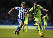 Huddersfield Town defender Joel Lynch (33) and Brighton striker (on loan from Manchester United), James Wilson (21) battle for the ball during the Sky Bet Championship match between Brighton and Hove Albion and Huddersfield Town at the American Express Community Stadium, Brighton and Hove, England on 23 January 2016.