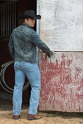 cowboy with a great ass by a barn