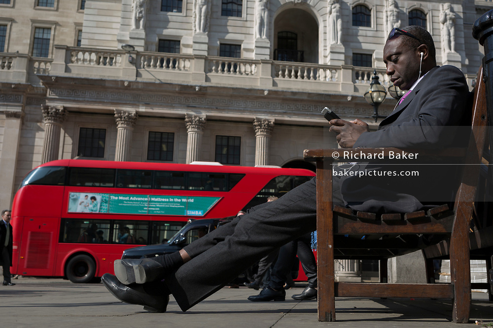 A businessman checks his messages opposite the Bank of England on Threadneedle Street in the City of London, the capital's financial district also known as the Square Mile, on 6th April 2017, in London, England.