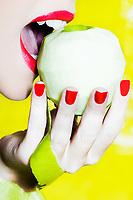 beautiful caucasian woman portrait biting an apple studio on yellow background