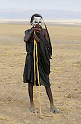Young Masai recently cirumsised wears white make-up markings and black robes until in a few weeks he adopts the full red colourful robes of a Masai Warrior