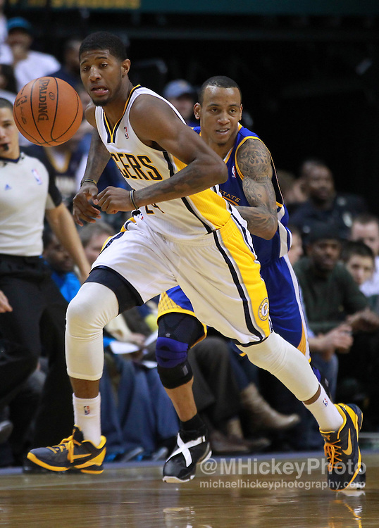 Feb. 28, 2012; Indianapolis, IN, USA; Indiana Pacers shooting guard Paul George (24) chases a loose ball as Golden State Warriors shooting guard Monta Ellis (8) follows from behind at Bankers Life Fieldhouse. Indiana defeated Golden State 102-78. Mandatory credit: Michael Hickey-US PRESSWIRE