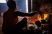 Ester Hodari, age 22 years old, cooks dinner using the traditional three-rock cook stove with a fire in the middle. These cookstoves use a lot of fuel, firewood, and produce a lot of smoke. Ester told us that cooking with this type of stove made her eyes turn red and she often had a chest cough. Her children, ages 5, 2 and 3 months are often with her when she is cooking. Her sister-in-law, Shadya Jumanne, age 11, helps her cook as well. Not long ago Ester&rsquo;s 3 month-old developed a cough, It kept getting worse and so they took her by motorcycle to the hospital at night. Ester started really worrying about this.  After this Ester and her husband agreed that they needed to buy a clean cookstove and started saving. The girl helping Ester cook in some of the images is her sister-in-law Shadya Jumanne, age 11.<br /> <br /> Ester met Solar Sister entrepreneur Fatma Mziray when she married her husband and moved to this village, Mforo near Moshi, Tanzania. Ester said that Fatma is like a mother to her in the village. When Fatma showed Ester the new wood stove she saw that is used less wood and produced less smoke.