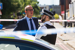 A detective speaks with a police officer at the cordon surrounding the scene where a man in his 40s was stabbed on Latchmere Road in Battersea in the afternoon of July 3rd 2019, dying later that evening in hospital.. London, July 04 2019.
