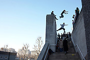 Leaping fearlessly across the gaps of high walls, teenage boys practice free-jumping over a stairwell in London's South Bank