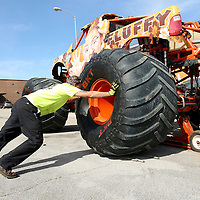 Adam Robison | BUY AT PHOTOS.DJOURNAL.COM<br /> Kevin King, owner and driver of the Monster Jam truck Fluffy, puts one of the 66 inch tall and 43 inch wide tires on the truck as he and crew worker Brandon Thong prepare the truck for the Monster Jam event once arriving at the BancorpSouth Arena on Thursday morning.