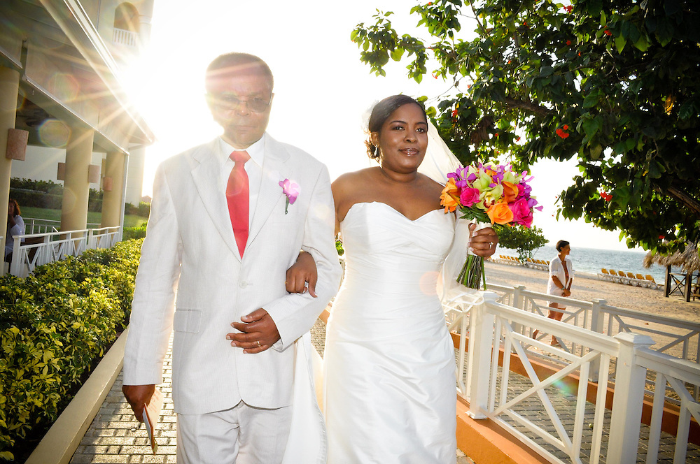 Lulu's father walks her down the path to the beach ceremony at Iberostar Rose Hall, Montego Bay, Jamaica