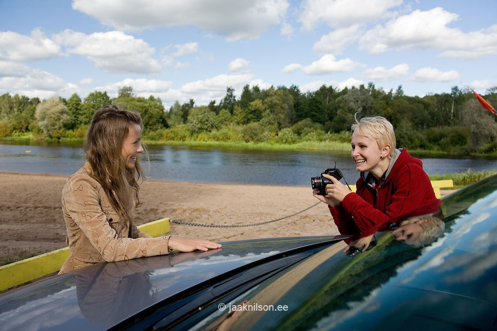 Young woman taking picture of happy smiling posing friend by car