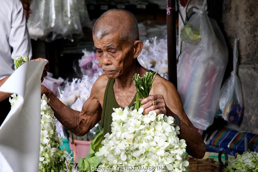 Street merchant selling flowers at an open market in Bangkok.