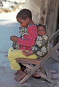 AFRICA, KENYA, KALIFI: Very young Kenyan girl with her sleeping baby brother on her back in a sling made of kanga cloth.