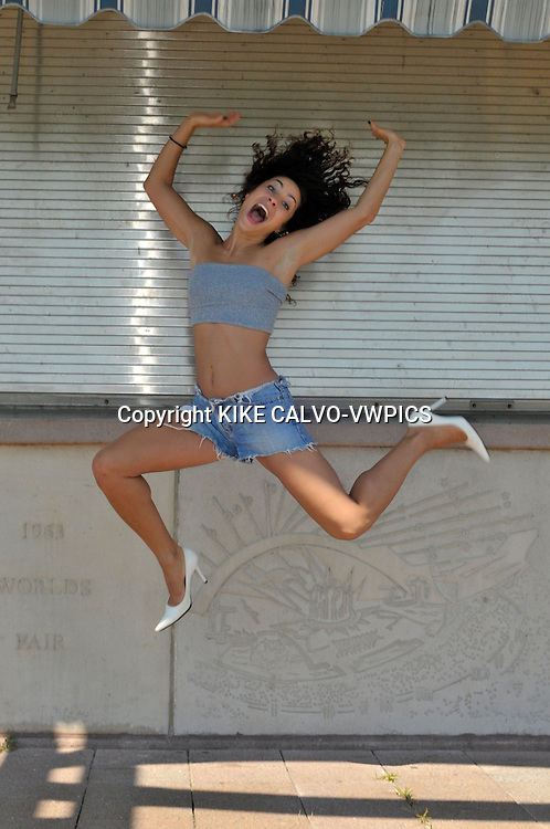 MR - Model released picture of a italian descent actress and dancer in Flushing Meadow Park in Queens., Happy woman jumping in short jeans and white pump shoes