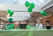Francisco Cintron, left, a sophomore studying history blows up an inflatable leprechaun while Breanna Hayman, right, a junior studying aviation management invites people to come over to pick up a stress ball, necklaces, and temporary tattoos during the Office of Diversity and Inclusion's St. Patrick's Day celebration on March 17, 2016.