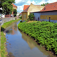 Eger-patak Flowing Through Eger, Hungary<br /> The Eger Creek flows through three cities and 13 villages during its 25 mile journey. This waterway was a vital source for irrigation and was populated with flour and sawmills from the 17th through the 19th centuries. Eger is located in the fertile River Eger Valley between the M&aacute;tra and B&uuml;kk mountain ranges. These hills are covered with vineyards. The city&rsquo;s name is derived from the Latin word &ldquo;ager&rdquo; which means &ldquo;earth.&rdquo; The river bisects the old town from the base of Castle Hill.