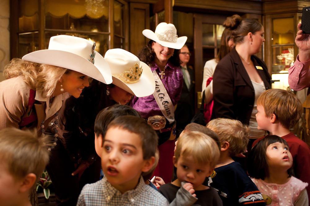 Sarah Wiens, Miss Rodeo Colorado 2013, left, and rodeo royalty greet children waiting in line to see the Grand Champion Steer at The Brown Palace Hotel in Denver.