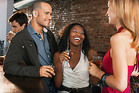 Couple with friend holding drinks laughing standing at bar