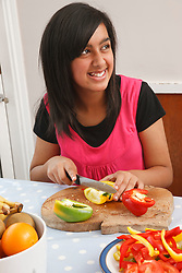 Teenager cutting tomatoes