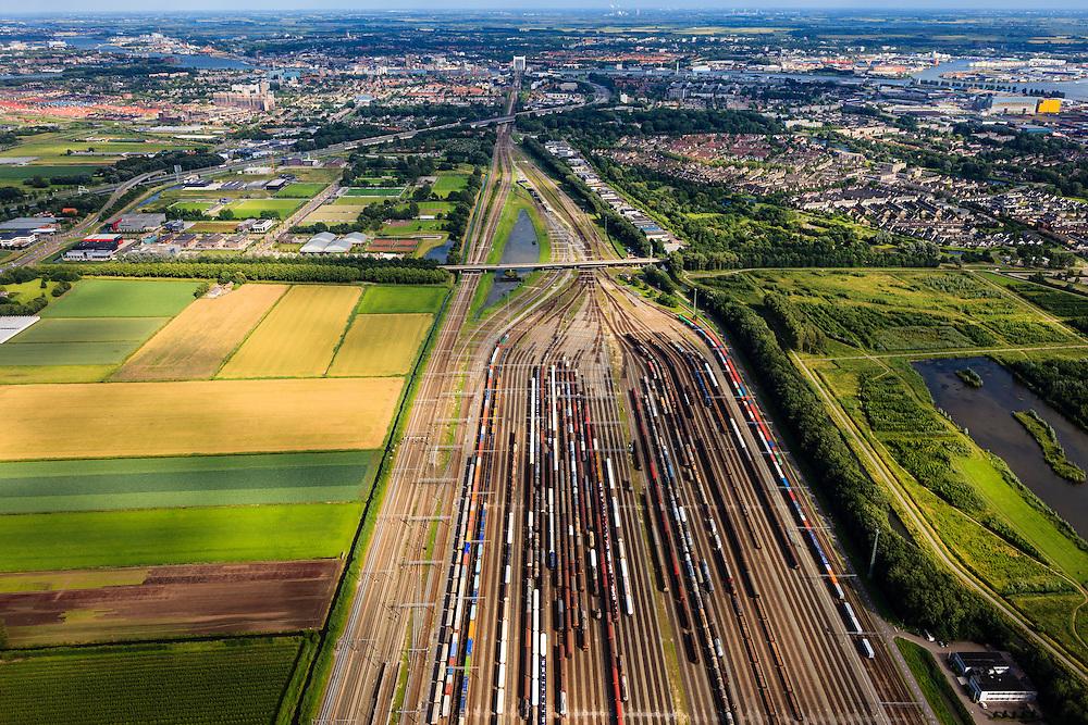 Nederland, Zuid-Holland, Zwijndrecht, 15-07-2012; Kijfhoek, rangeerterrein voor goederentreinen. Overzicht van de verdeelsporen met onder in beeld de railremmen, spoorbrug van Dordrecht aan de horizon..Kijfhoek huisvest Keyrail, exploitant Betuweroute en is in beheer bij ProRail. De Betuweroute, die begint als Havenspoorlijn op de Maasvlakte, verbindt via Kijfhoek de Rotterdamse haven met het achterland. Het rangeeremplacement dient voor het sorteren van goederenwagons waarbij gebruik gemaakt wordt van de zwaartekracht, het 'heuvelen': de wagons worden de heuvel opgeduwd, bij het de heuvel afrollen komen ze, door middel van wissels, op verschillende verdeelsporen. Railremmen zorgen voor het automatisch remmen van de wagons. Na het heuvelproces staan de nieuw samengestelde treinen op aparte opstelsporen..Kijfhoek, railway yard used by ProRail and Keyrail (Betuweroute operator). Kijfhoek connects via the Betuweroute (beginning as Havenspoorlijn on the Maasvlakte), through the port of Rotterdam with the hinterland. The shunting yard for sorting wagons makes use of gravity. The new trains are assembled on separate tracks..luchtfoto (toeslag), aerial photo (additional fee required).foto/photo Siebe Swart