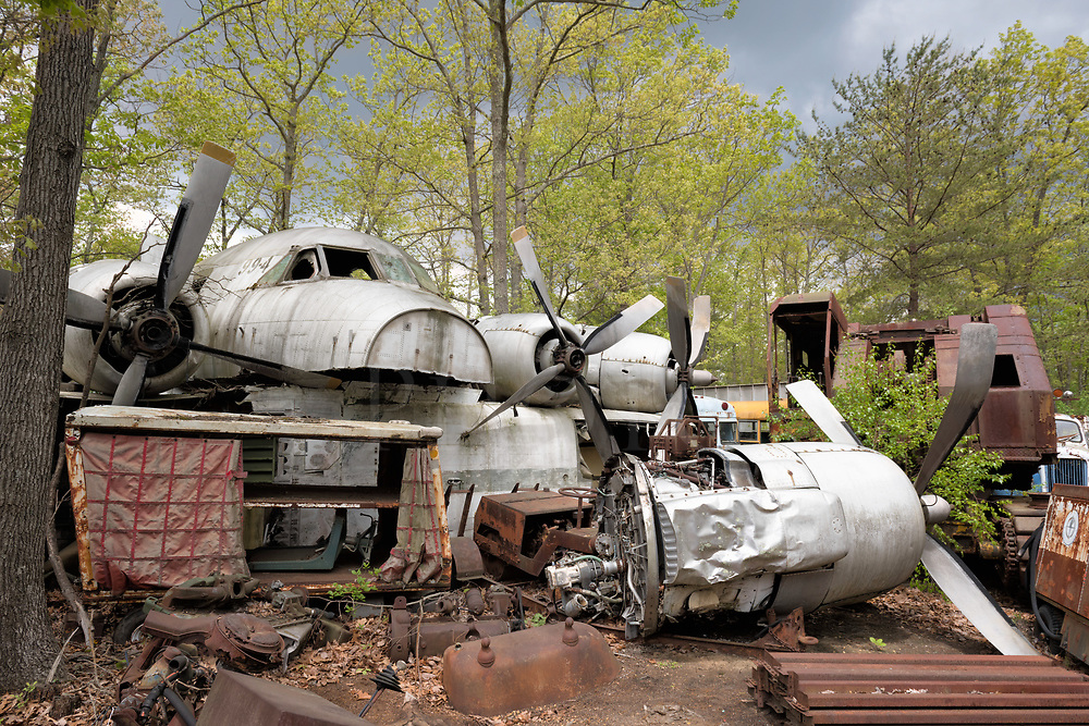 Looks like the old 99-4 is laid up in a salvage boneyard with no parole in sight because those dents and damage are permanent, which means fini. Actually, what appears to be a whole airplane is simply frankensteined together for appearances with the fuselage laid perpendicularly across several other plane bodies, and some engines with props set down in line beside it. There are no wings which have been cut off to transport it here, and not enough room to put four engines up there which leaves one lollygagging on the ground with a bent prop. If you look closely, the fuselage has been split lengthwise with the bottom missing. Here is a good example of owner-initiated impromptu junkyard sculpture...in other words, creative junking!<br />