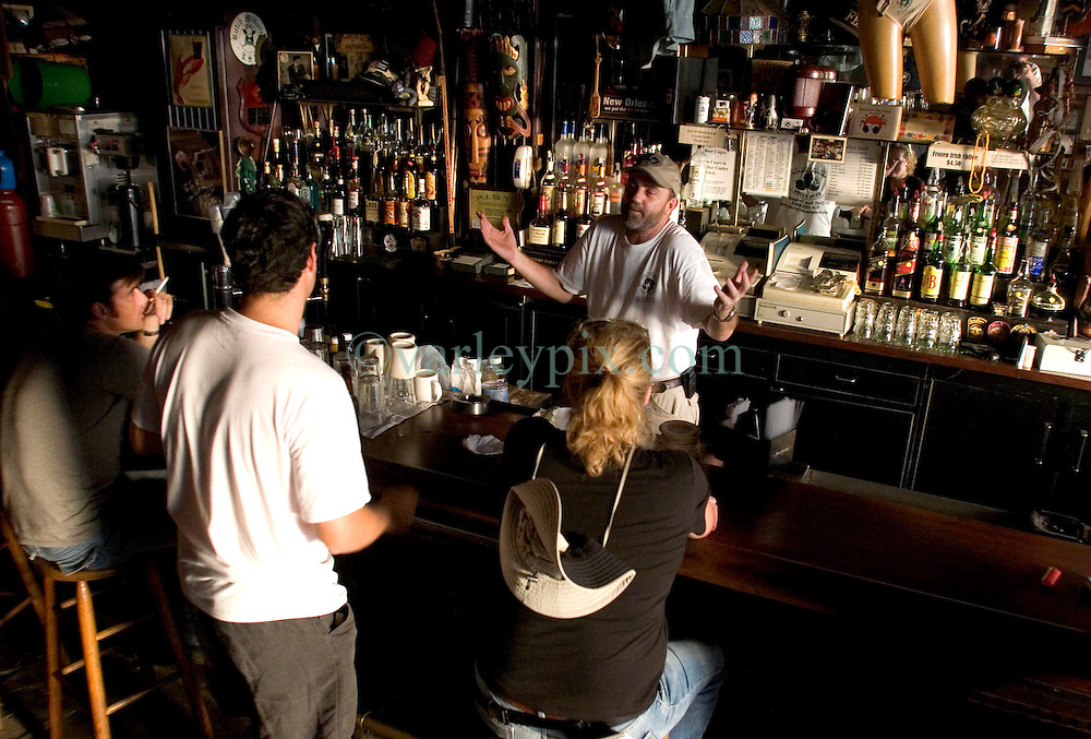 10 Sept 2005. New Orleans, Louisiana.  Hurricane Katrina aftermath.<br /> Jim Monaghan, the barman at Molly's  bar on Decatur Street talks with customers. The famous French Quarter bar remained open throughout the days following the storm.<br /> Photo; &copy;Charlie Varley/varleypix.com