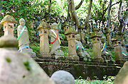 "Photo shows some of the Gohyaka Rakan – more than 500 stone statues depicting ""arhat"" – disciples of  Buddha who attained nirvana inside the Toyama Folk Village in Toyama Prefecture Japan. Each statue is draped in colorful sashes and lined up on a steep hillside within the grounds of Chokeiji temple."