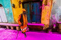 A saddhu (Holy man) walks down the street after a procession has passed throwing colored powders, Chhadi Mar Holi ( a local celebration during Holi, festival of colors), Gokul, near Mathura, Uttar Pradesh, India.