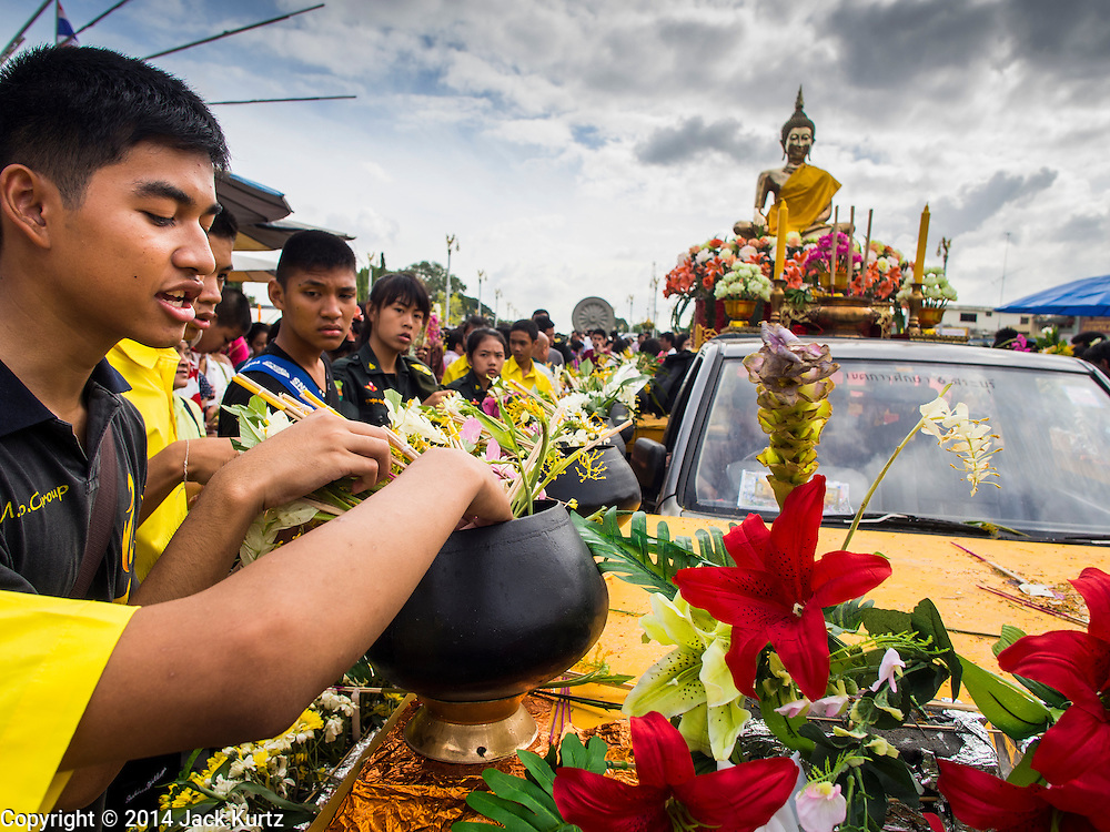 """12 JULY 2014 - PHRA PHUTTHABAT, SARABURI, THAILAND: People put flowers on the temple's car during the Tak Bat Dok Mai at Wat Phra Phutthabat in Saraburi province of Thailand. Wat Phra Phutthabat is famous for the way it marks the beginning of Vassa, the three-month annual retreat observed by Theravada monks and nuns. The temple is highly revered in Thailand because it houses a footstep of the Buddha. On the first day of Vassa (or Buddhist Lent) people come to the temple to """"make merit"""" and present the monks there with dancing lady ginger flowers, which only bloom in the weeks leading up Vassa. They also present monks with candles and wash their feet. During Vassa, monks and nuns remain inside monasteries and temple grounds, devoting their time to intensive meditation and study. Laypeople support the monks by bringing food, candles and other offerings to temples. Laypeople also often observe Vassa by giving up something, such as smoking or eating meat. For this reason, westerners sometimes call Vassa """"Buddhist Lent.""""    PHOTO BY JACK KURTZ"""