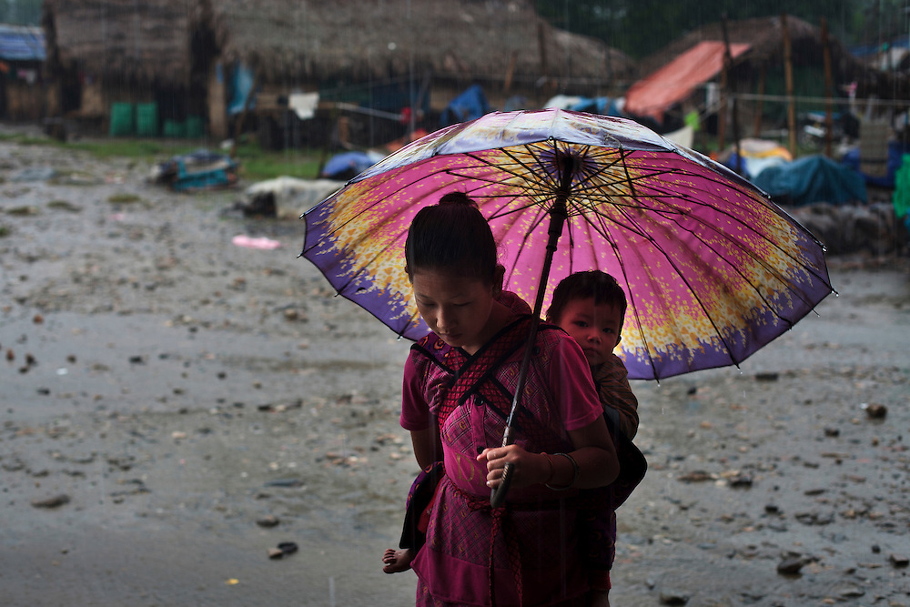 A Kachin woman keep from the rain with an umbrella in Woi Chyai Internal Displacement People (IDP) refugee camp near to Laiza village close to the China border, Myanmar on July 23, 2012. According to KIO sources around 50000 Kachin people live as refugees in those camps.