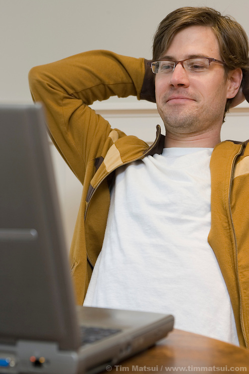 A caucasian man sits alone at home working on his wireless, wi-fi, laptop computer.