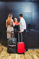 Portrait of business couple checking in at hotel lobby
