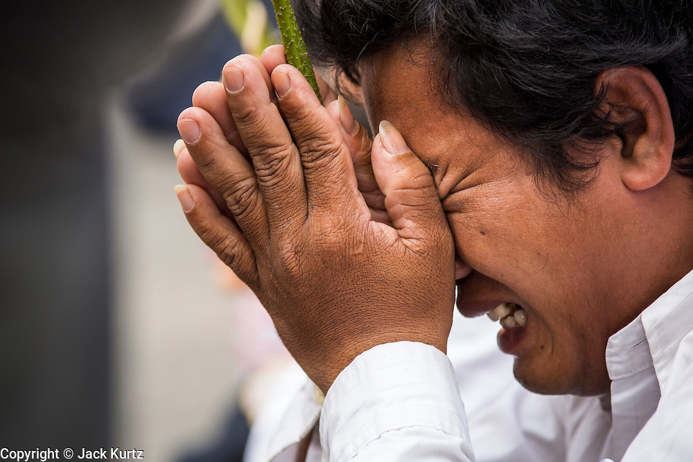 "01 FEBRUARY 2013 - PHNOM PENH, CAMBODIA: A man cries in grief as the funeral procession of former Cambodian King Norodom Sihanouk passes him in Phnom Penh. Norodom Sihanouk (31 October 1922 - 15 October 2012) was the King of Cambodia from 1941 to 1955 and again from 1993 to 2004. He was the effective ruler of Cambodia from 1953 to 1970. After his second abdication in 2004, he was given the honorific of ""The King-Father of Cambodia."" Sihanouk died in Beijing, China, where he was receiving medical care, on Oct. 15, 2012. His cremation is will be on Feb. 4, 2013. Over a million people are expected to attend the service.    PHOTO BY JACK KURTZ"