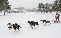 Bill Boyd of Merrimack NH passes by the Laconia Country Club House during the six dog class series of the 84th Annual Laconia World Championship Sled Dog Derby Friday morning.   (Karen Bobotas/for the Laconia Daily Sun)