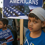 "American Muslim boy holding sign ""We Are Muslim Americans""one of the many faces of people showing her ethnic pride who were marching and in the crowds from the 2016 Muslim Day Parade in New York."
