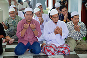 """Sept. 25, 2009 -- PATTANI, THAILAND: Men gather for Friday prayers in the Central Mosque in Pattani, Thailand. The mosque's Imam said a special prayer on this day for the Thai King who is in a hospital in Bangkok. Pattani's Central Mosque is considered the most architecturally striking mosque in Thailand and was a leading tourist site until the current violence put an end to mass tourism in Pattani. Thailand's three southern most provinces; Yala, Pattani and Narathiwat are often called """"restive"""" and a decades long Muslim insurgency has gained traction recently. Nearly 4,000 people have been killed since 2004. The three southern provinces are under emergency control and there are more than 60,000 Thai military, police and paramilitary militia forces trying to keep the peace battling insurgents who favor car bombs and assassination.  Photo by Jack Kurtz / ZUMA Press"""