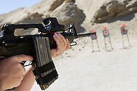 Man aiming machine gun at firing range, close up of hands