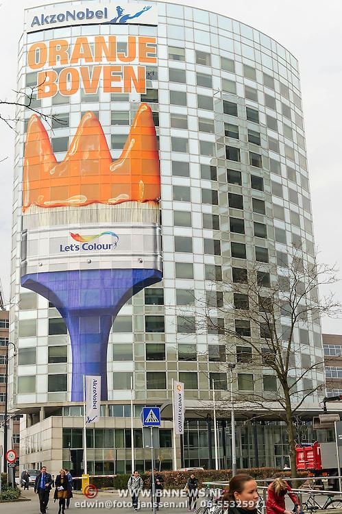 Amsterdam, 25-04-2013. Ter voorbereiding op de abdicatie/inhuldiging op 30 april zijn verschillende gebouwen, ondernemingen versiert. Het hoofdkantoor van Akzo Nobel aan de Strawinskylaan te Amsterdam is versiert met een grote oranje kwast en de tekst Oranje Boven,