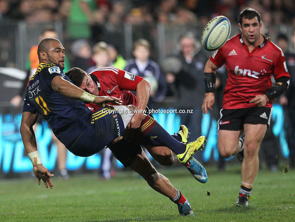 Patrick Osborne of the Highlanders is tackled in the process of passing the ball by Kieron Fonotia of the Crusaders during the Investec Super Rugby game between Crusaders v Highlanders at AMI Stadium, Christchurch. 12 July 2014 Photo: Joseph Johnson/www.photosport.co.nz