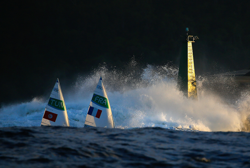 Ines Gmati from Tunisia and Mathilde de Kerangat from France sail past breaking waves as they return to harbour at the end of the day after a Laser Radial Womens race in the Rio 2016 Olympic Games Sailing events in Rio de Janeiro, Brazil, 12 August 2016.