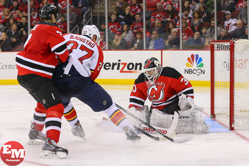Mar 31, 2014; Newark, NJ, USA; New Jersey Devils goalie Martin Brodeur (30) makes a save on Florida Panthers center Nick Bjugstad (27) while New Jersey Devils defenseman Mark Fayne (7) defends during the second period at Prudential Center.