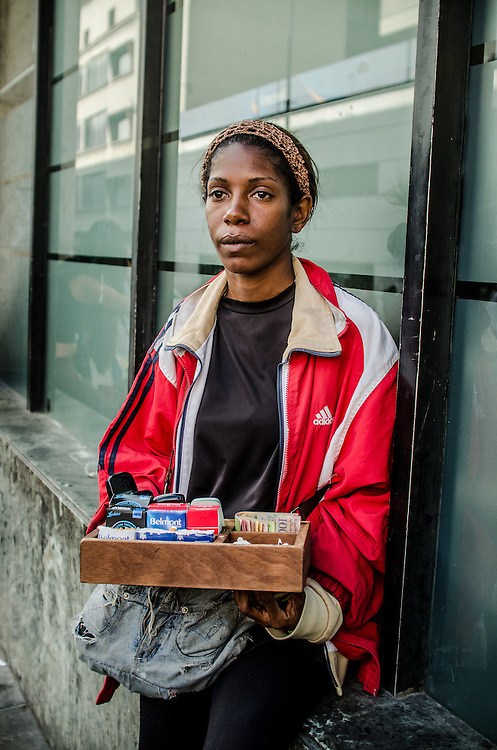 CARACAS, VENEZUELA - FEBRUARY 10, 2017:  Katiuska Tovar, 29, poses for a portrait with the box she uses to sell cigarettes and candies on the street in downtown Caracas. Ms. Tovar was once worked for the government as an administrative assistant, but had to leave when the government changed payment policies. Ms. Tovar struggles to buy enough food to feed herself and her son with the earnings she makes, so she supplements their diet with food scraps from the garbage. Despite her struggles, she still makes sure her son goes to school, and he earns some of the highest grades in his class. The 2016 ENCOVI (Survey on Living Conditions in Venezuela) found that a skyrocketing percentage of Venezuelan families are struggling to acquire enough food to eat.  Over 90% of the over 6,000 families surveyed reported not having enough income to buy all the food they need. A shocking 73% of survey respondents reported involuntarily weight loss, an average of 8.7kg each for those that said they involuntarily lost weight.  Food and medicine shortages, skyrocketing inflation and the collapse of social programs are causing working class families that once supported the government and Hugo Chávez's socialist revolution to increasingly become disillusioned with the government, and its commitment to the poor. Many once die-hard Chavistas say they feel abandoned, and no longer support the government. PHOTO: Meridith Kohut