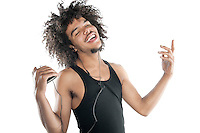 Portrait of a happy young man gesturing while listening to mp3 player over white background
