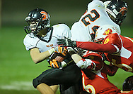Solon's Chris McNutt (4) holds onto the ball as he is pulled down by Marion's Evan Kramer (6) and Jordan Keeton (65) after a catch during the first half of the game between the Solon Spartans and the Marion Indians at Thomas Park Field in Marion on Friday evening, October 5, 2012.
