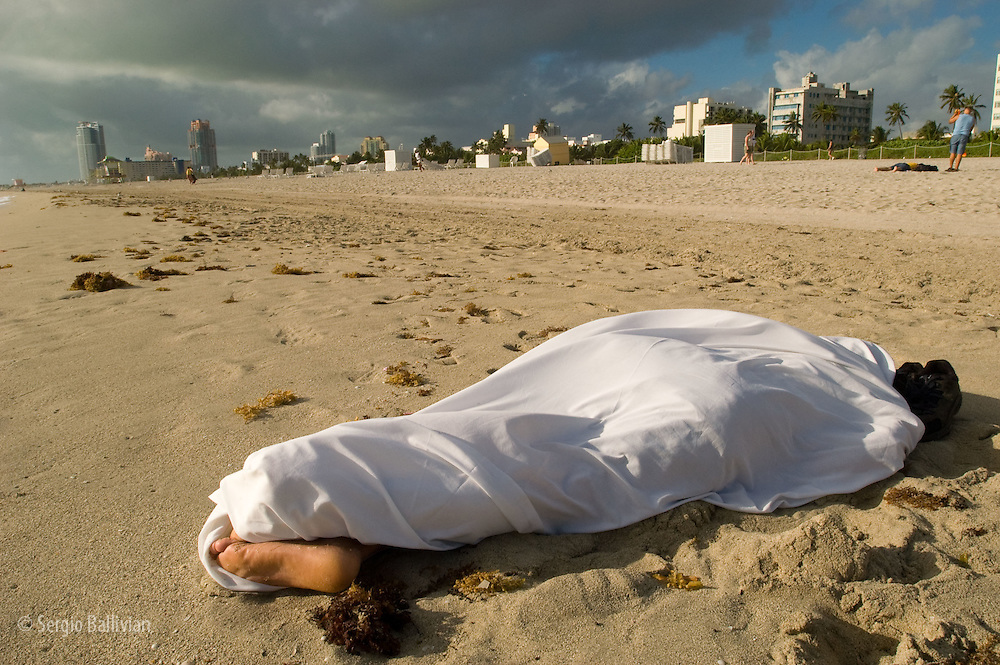 Someone sleeping wrapped in a sheet on a beach by the Atlantic Ocean in Miami Beach, Florida