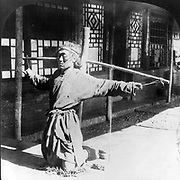 Chinese justice: Prisoner, kneeling on chains, ankles in a form of stocks, oustretched  arms supported by thumbs tied by cord to a pole. One of a pair of images from a stereographic card c1906. Criminal