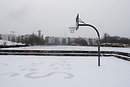 A basketball net standing on a snow-covered section of the Mauerpark, a space dedicated to recreation along the route of the former Berlin Wall north of the city centre. The route of the Wall, which stood from 1962-1989, has been developed into the 'Mauerweg,' a thoroughfare which traces most of the route of the Wall which encircled the city and divided it into East and West Berlin during the Cold War. In the years following the 1989 civil uprising in the German Democratic.Republic, most of the Wall was removed as part of the reunification strategy which united the pro-Soviet DDR and the Federal Republic of (West) Germany.