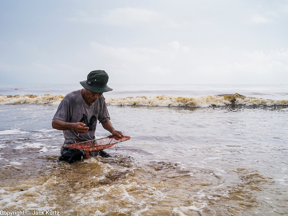 04 NOVEMBER 2012 - KAO SENG, SONGKHLA, THAILAND:  A man looks for snails and clams in the surf in Kao Seng. Kao Seng is a traditional Muslim fishing village on the Gulf of Siam near the town of Songkhla, in the province of Songkhla. In general, their boats go about 4AM and come back in about 9AM. Sometimes the small boats are kept in boat because of heavy seas or bad storms.    PHOTO BY JACK KURTZ