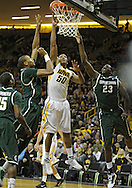 February 2 2011: Iowa Hawkeyes forward Jarryd Cole (50) puts up a shot between Michigan State Spartans center Adreian Payne (5) and Michigan State Spartans forward Draymond Green (23) during the first half of an NCAA college basketball game at Carver-Hawkeye Arena in Iowa City, Iowa on February 2, 2011. Iowa defeated Michigan State 72-52.