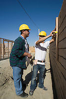 Construction workers measuring brick wall