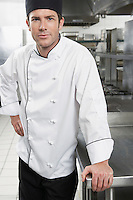 Male chef with hand on hip in kitchen portrait